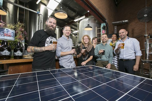 Oscar McMahon (l) of Young Henry's and members of a communtiy solar project pose for a photograph with a solar panel inside the Young Henry's brewery. (photo by Jamie Williams/City of Sydney)